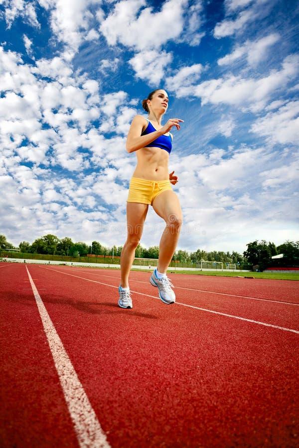 Rüttelnde und laufende Übung der jungen Frau stockfoto