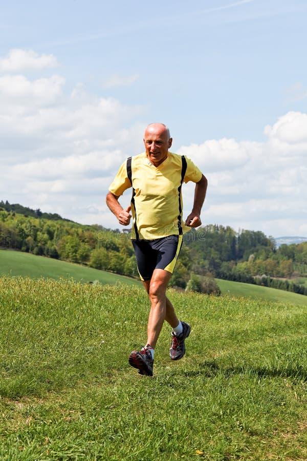 Rüttelndes Laufen des älteren Mannes auf Wiese lizenzfreies stockbild