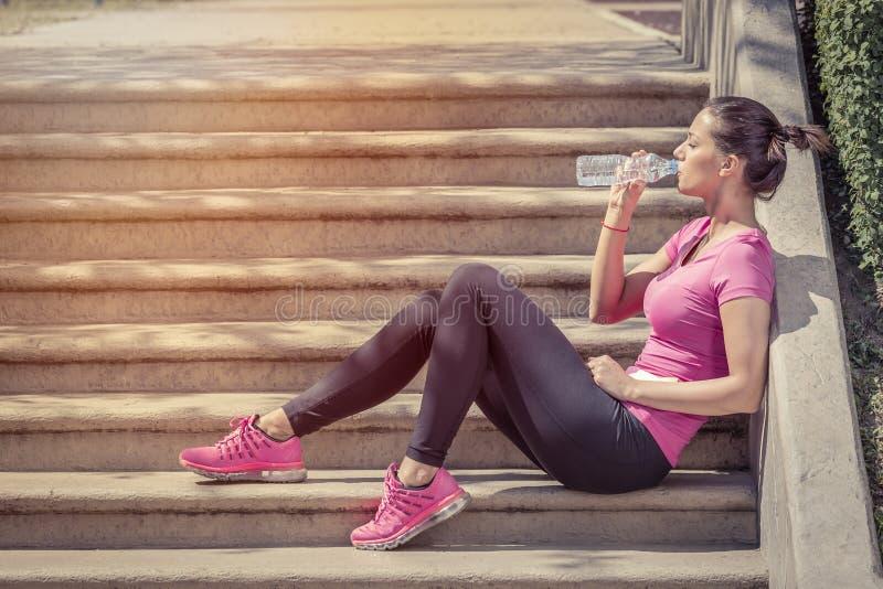 Rüttler, der auf Treppe und Trinkwasser nach Übung sitzt lizenzfreies stockfoto