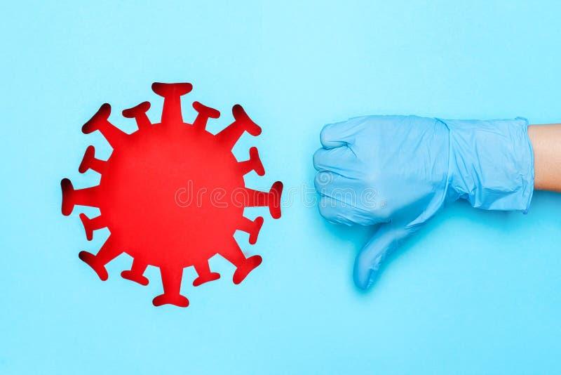 Rączka w rękawiczce medycznej ukazująca niepodobny gest i czerwony koronawirus, wirus, bakterie, mikroby na niebieskim tle Koncep zdjęcie stock