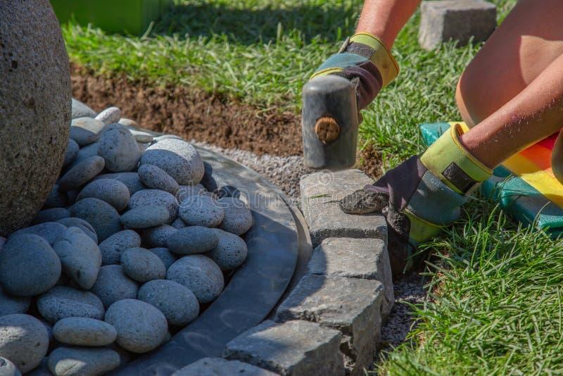 Ręce hobby robotnika z rękawiczkami roboczymi układającymi kostki bazaltowe w krawężnik fontanny ogrodowej zdjęcie stock