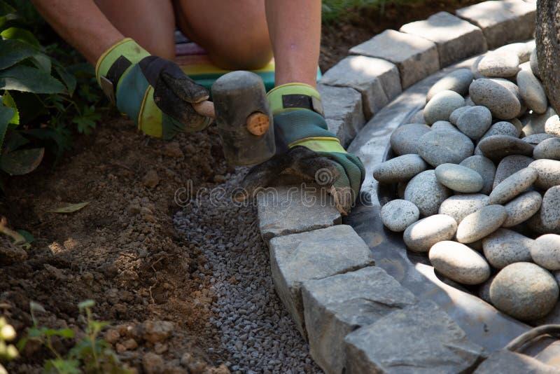 Ręce hobby robotnika z rękawiczkami roboczymi układającymi kostki bazaltowe w krawężnik fontanny ogrodowej fotografia stock