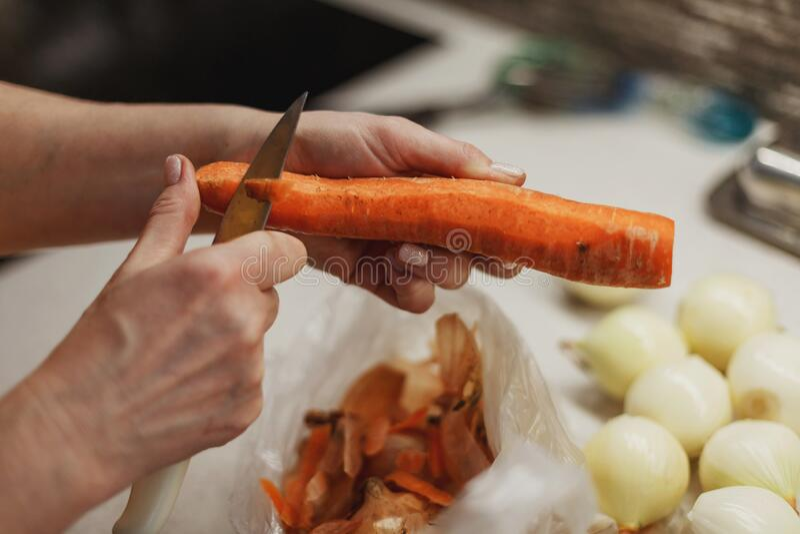 Ręce kobiety w trakcie obierania świeżej marchewki nad plastikową torbą zdjęcia stock