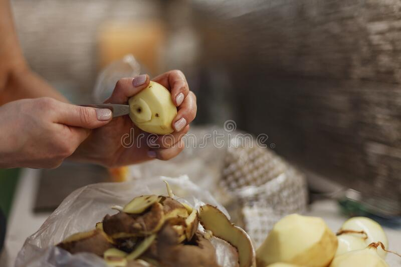 Ręce kobiety w trakcie obierania nieumytego ziemniaka nad plastikową torbą obrazy stock