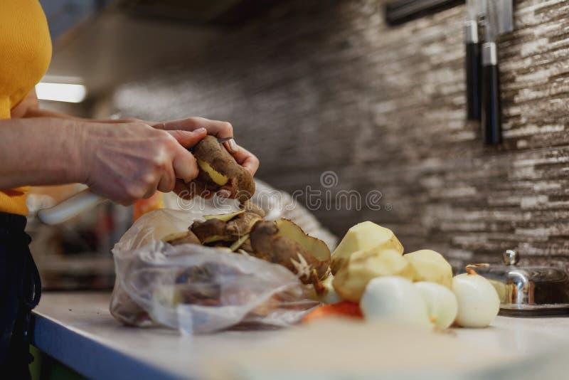 Ręce kobiety w trakcie obierania nieumytego ziemniaka nad plastikową torbą obrazy royalty free
