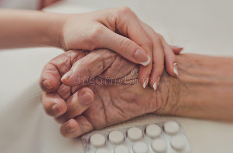 ręce mi Ręka młoda kobieta ostrożnie wspiera marszczącą rękę stara kobieta zdjęcia stock