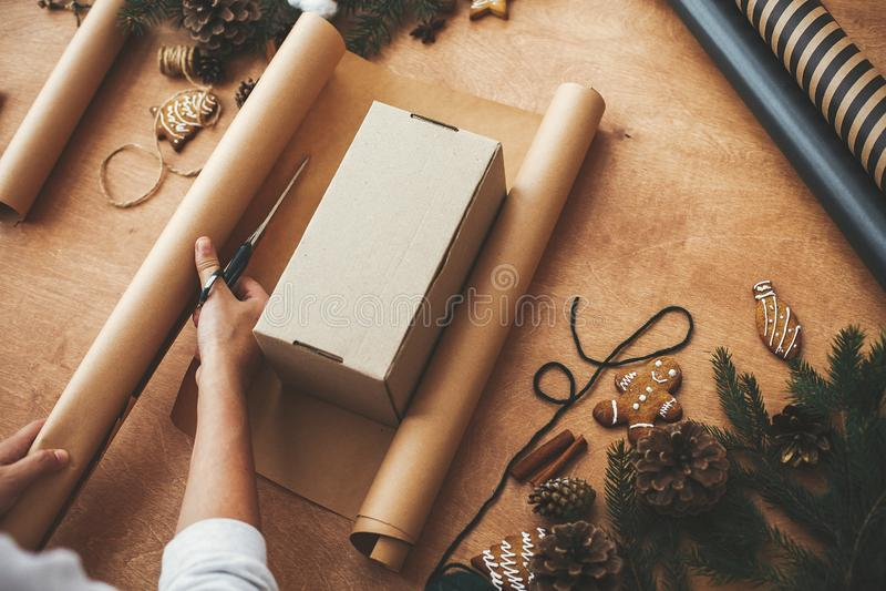 Ręce tnące papier opakowaniowy nożyczkami i pudełkiem na prezent, gałęzie sosnowe, stożki, ciastka z piernika, nici, cynamonu, no obraz stock