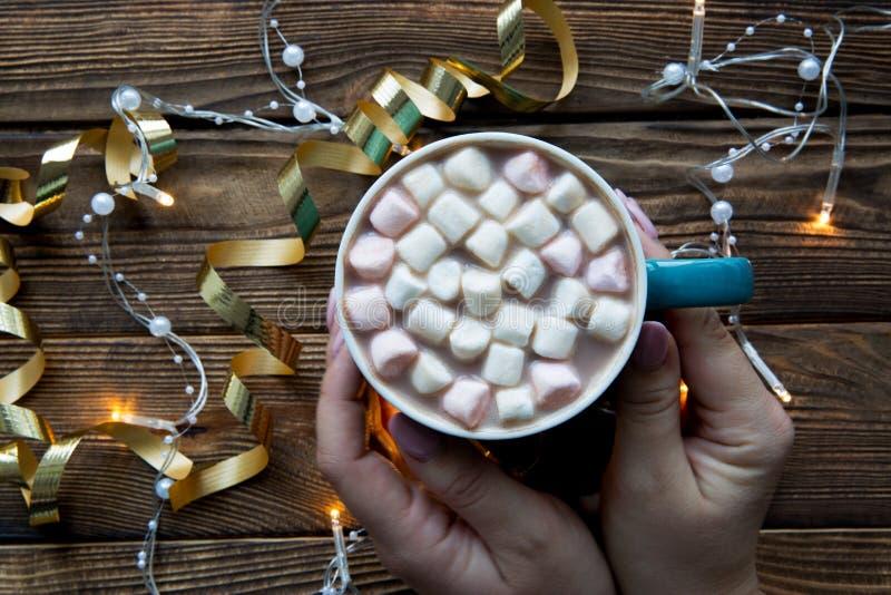 Ręce trzymające filiżankę kakao na rustycznym stole Światła świąteczne, złote dekoracje obraz stock