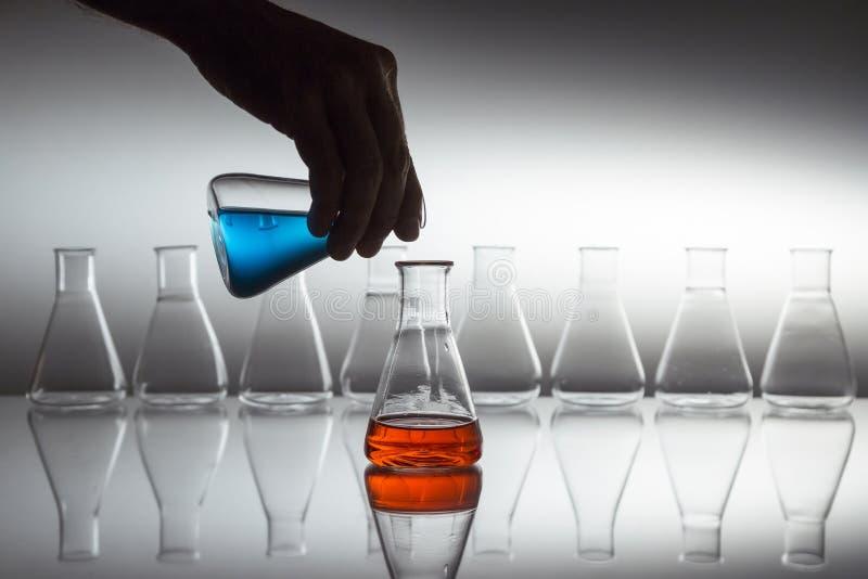 Ręczne wlewanie niebieskiego do czerwonego płynu w kolbie szklanej szklanej laboratoryjnej kolby z wyposażeniem szklanym na powie obraz stock