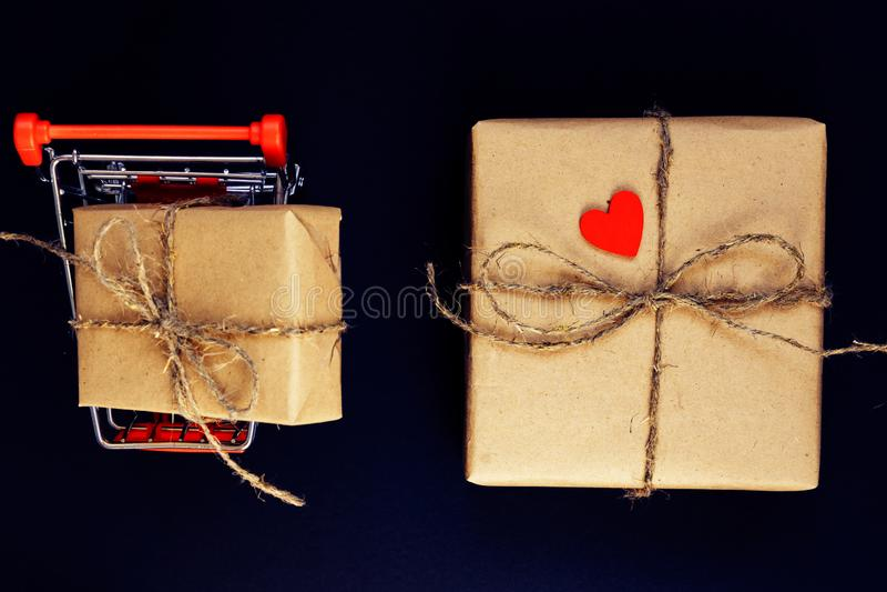 RÄ™cznie obrobione pudeÅ'ko na prezent, owiniÄ™te papierem z czerwonym drewnianym sercem i linÄ… w koszyku zabawek, na czarnym tle zdjęcie stock