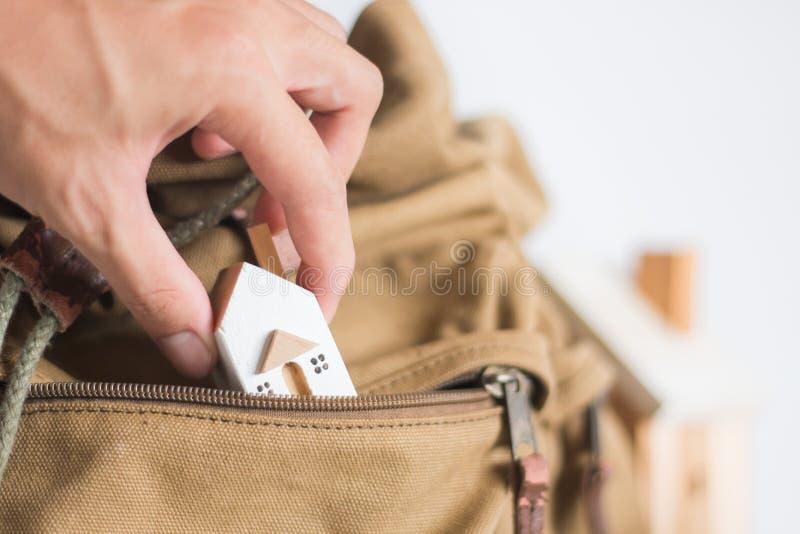 RÄ™cznie weź model domu miniaturowego w brÄ…zowej kieszeni Zipper na biaÅ'ym tle zdjęcia royalty free