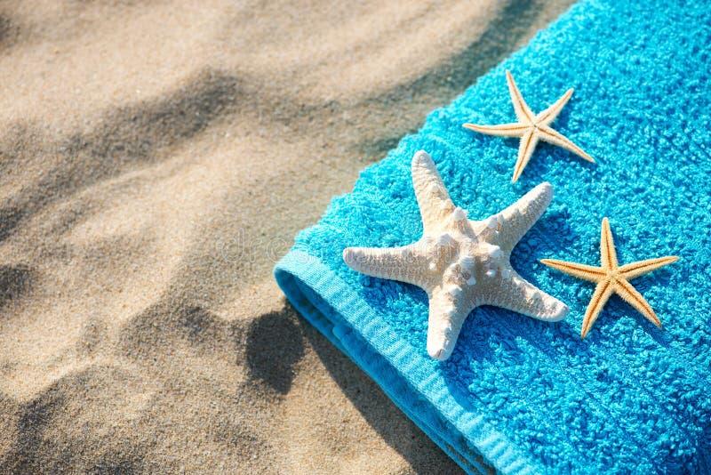 Ręcznik koncepcyjny wakacji letnich z okularami przeciwsłonecznymi i rozgwiazdami na piaszczystej plaży tropikalnej obraz royalty free