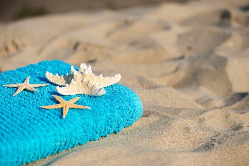 Ręcznik koncepcyjny wakacji letnich z okularami przeciwsłonecznymi i rozgwiazdami na piaszczystej plaży tropikalnej fotografia stock