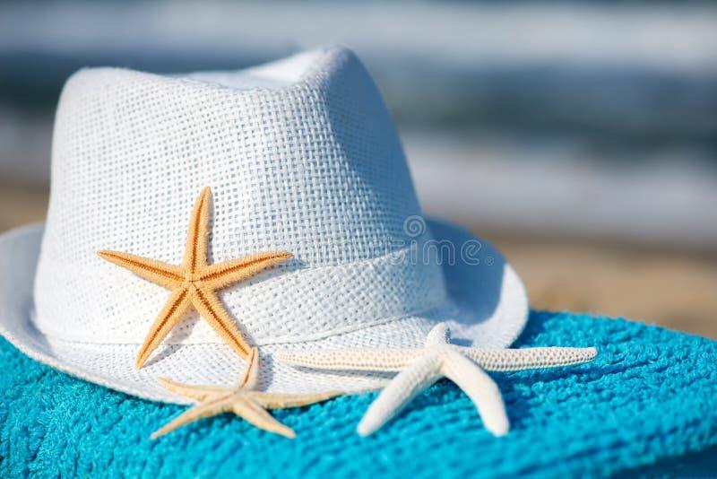 Ręcznik koncepcyjny wakacji letnich z okularami przeciwsłonecznymi i rozgwiazdami na piaszczystej plaży tropikalnej obrazy stock