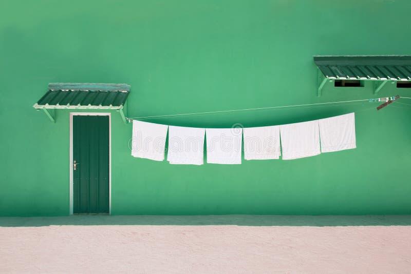 Ręczniki na clothesline blisko zielonego domu jak bungalow z zielonym drzwi zdjęcia stock
