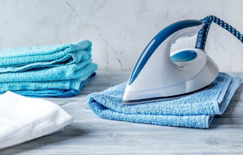 Ręczniki wypiętrzają z żelazem w housekeeping ustawiającym na laudry tle obraz royalty free