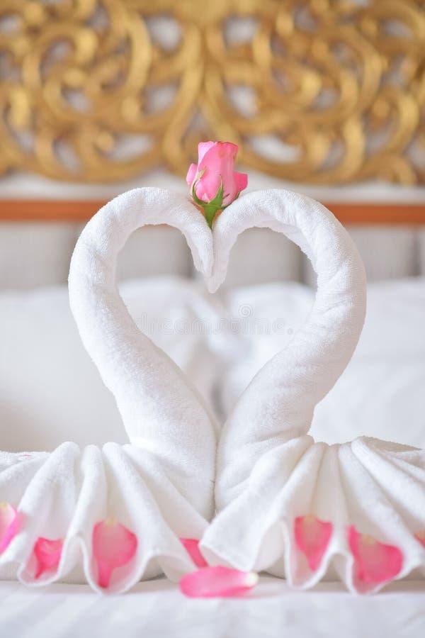 Ręcznikowi łabędź na łóżku w hotelu obrazy stock