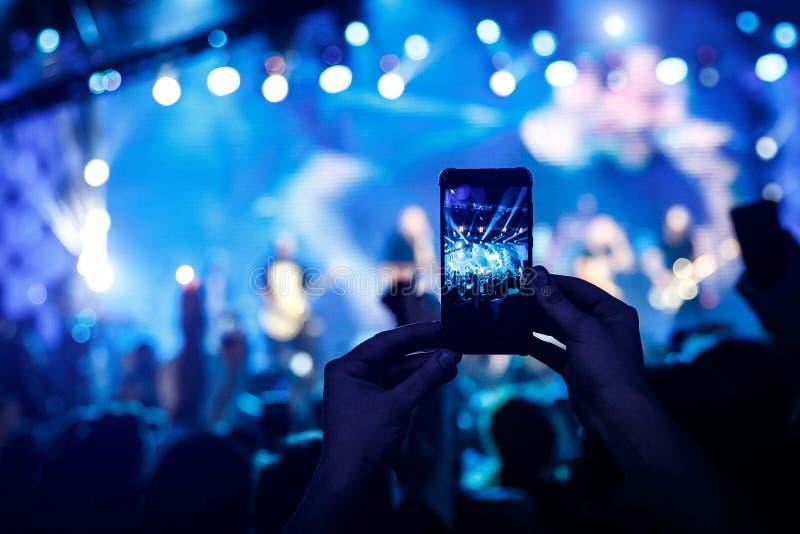 Ręczny mądrze telefon filmuje koncert fotografia stock