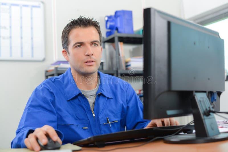 Ręczny pracownik siedzący przy biurkiem zdjęcie stock