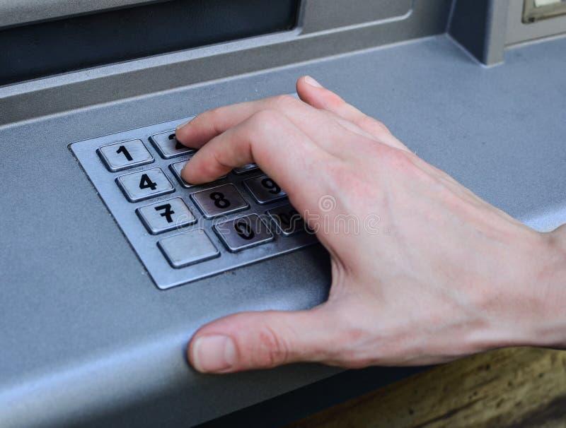 Ręk wchodzić do liczby na ATM maszynie obraz stock