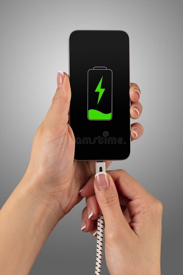 Ręka ładuje telefon obraz stock