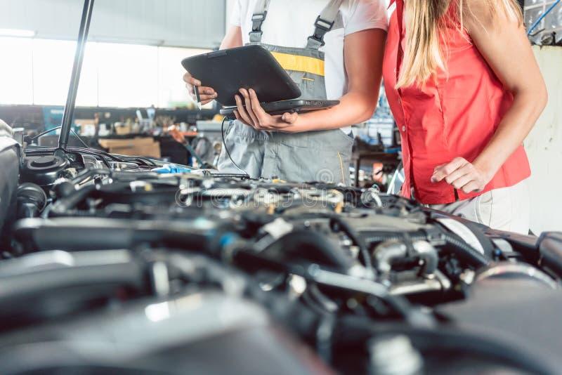 Ręka auto mechanik otwiera nafcianego rezerwuar podczas gdy sprawdzać samochód obrazy stock
