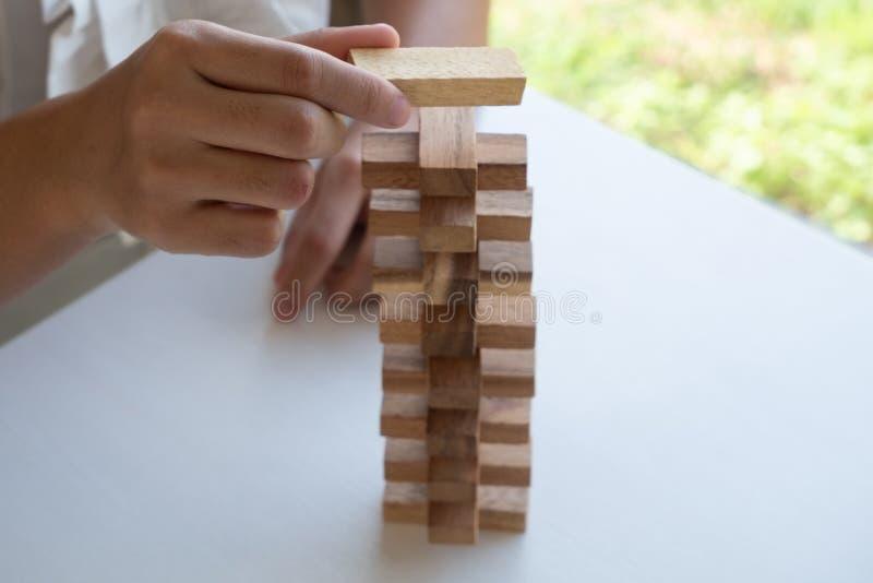 Ręka bawić się blok drewnianą grę, uprawia hazard umieszczający drewnianego blok Pojęcia ryzyko zarządzania i strategii plan obrazy royalty free