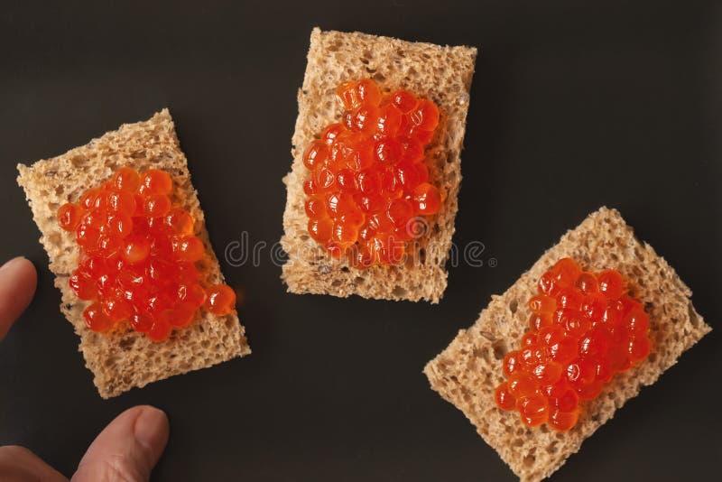 Ręka bierze jeden trzy kanapki, canapes z naturalnym czerwonym kawiorem łosoś łowi na czarnym tle, odgórny widok fotografia royalty free
