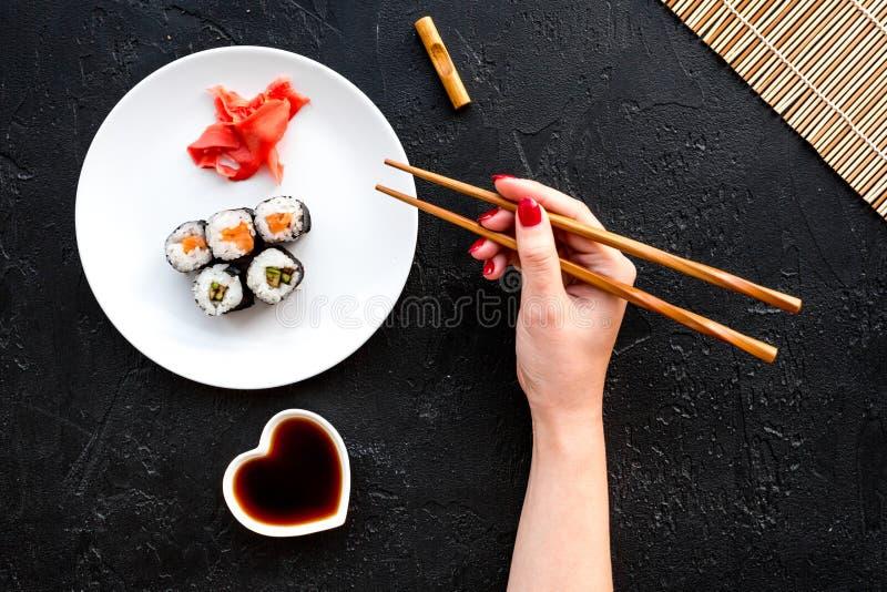 Ręka bierze suszi rolkę z łososiem i avocado z chopstick Czarnego tła odgórny widok fotografia stock