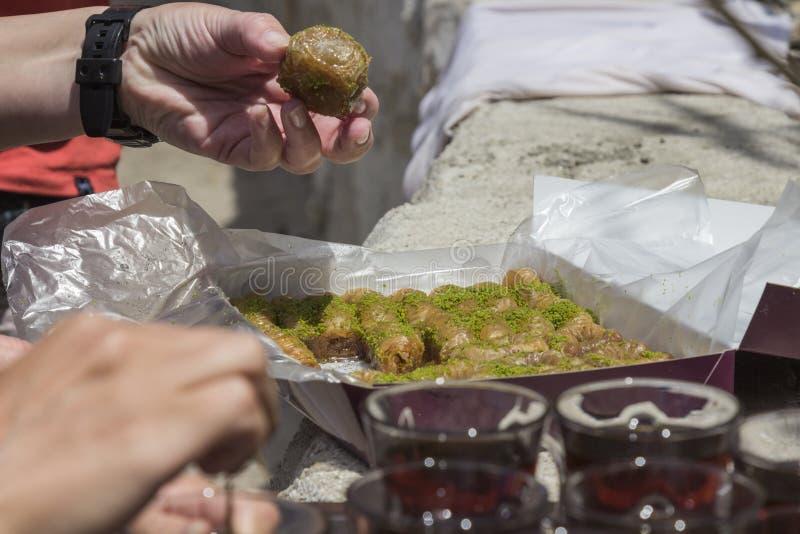 Ręka bierze wschodnią słodkość od pudełka, szkła herbata, w górę fotografia royalty free