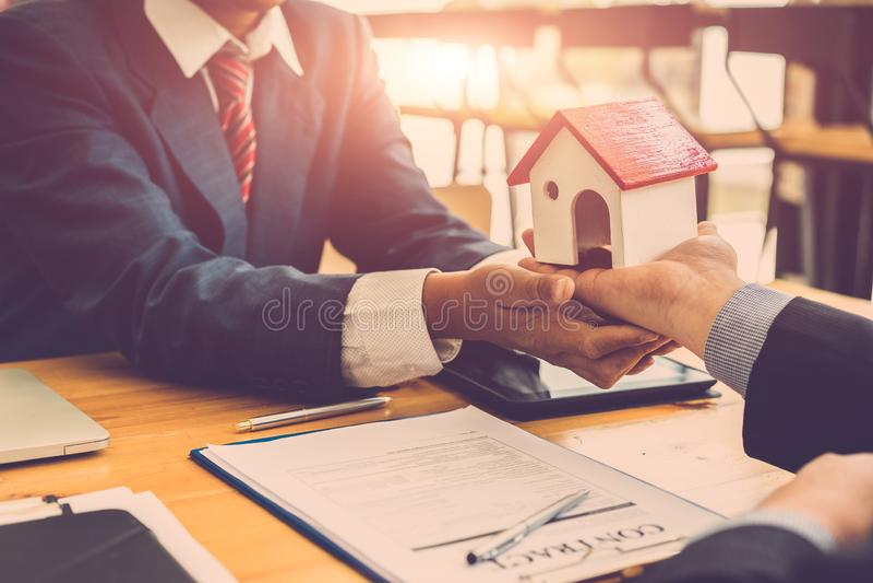 Ręka biznesmen podpisuje kontraktacyjnej zgody dokument, kupuje nowego dom, kredyt mieszkaniowy, rusza się do domu lub dzierżawi  zdjęcia stock