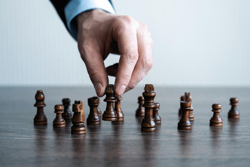 ręka biznesmen poruszająca szachowa postać w turniejowej sukces sztuce strategii, zarządzania lub przywódctwo pojęcie, fotografia royalty free