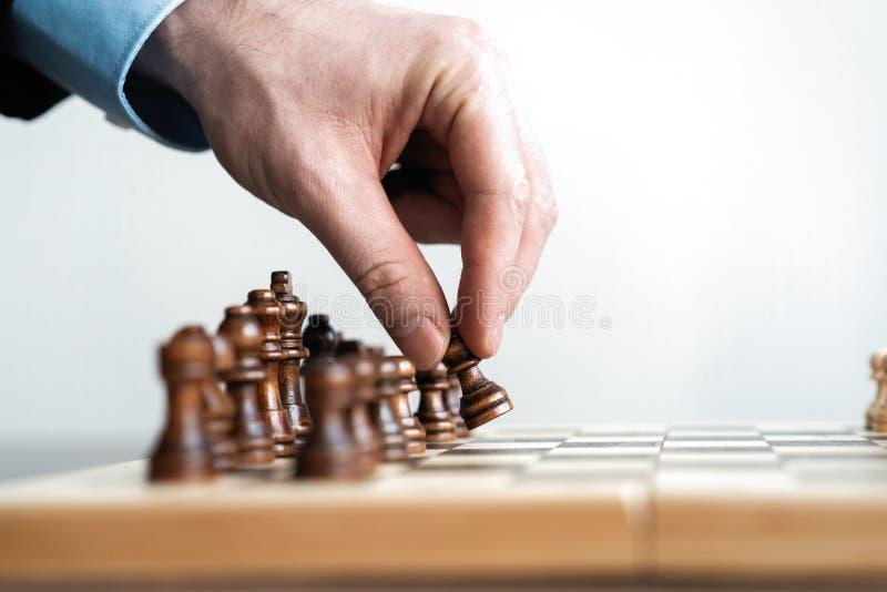 ręka biznesmen poruszająca szachowa postać w turniejowej sukces sztuce strategii, zarządzania lub przywódctwo pojęcie, fotografia stock