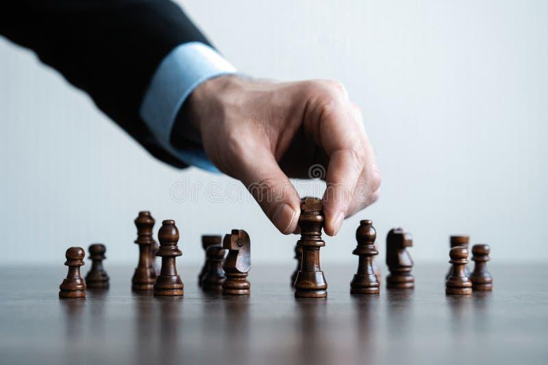 ręka biznesmen poruszająca szachowa postać w turniejowej sukces sztuce strategii, zarządzania lub przywódctwo pojęcie, zdjęcia stock
