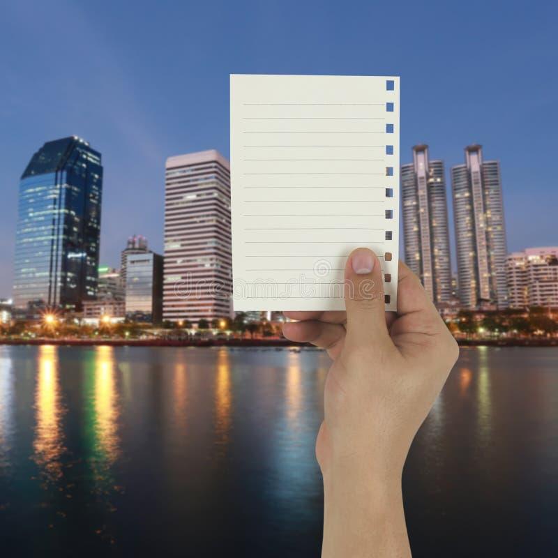 Ręka biznesmen trzyma pustą papier notatkę na zmierzchu c zdjęcie royalty free