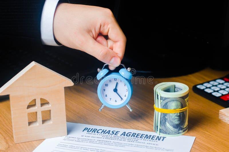 Ręka biznesmen utrzymuje budzika na kontrakcie dla zakupu własność lub nieruchomość Mały czas, limitowany obraz royalty free
