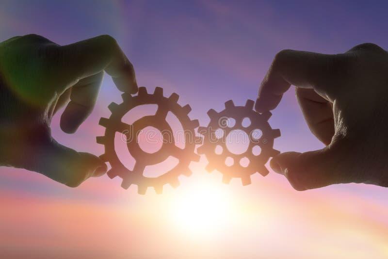 Ręka biznesmena mienia przekładnie na tle niebo w słońcu, łączy łamigłówka kawałki tworzenie mechanizm zdjęcie stock