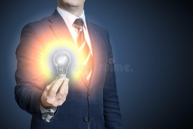 Ręka biznesmena mienie iluminował żarówki, pomysłu, innowaci i inspiraci pojęcie, Jaskrawy pomysł w ręka biznesmenie obraz stock