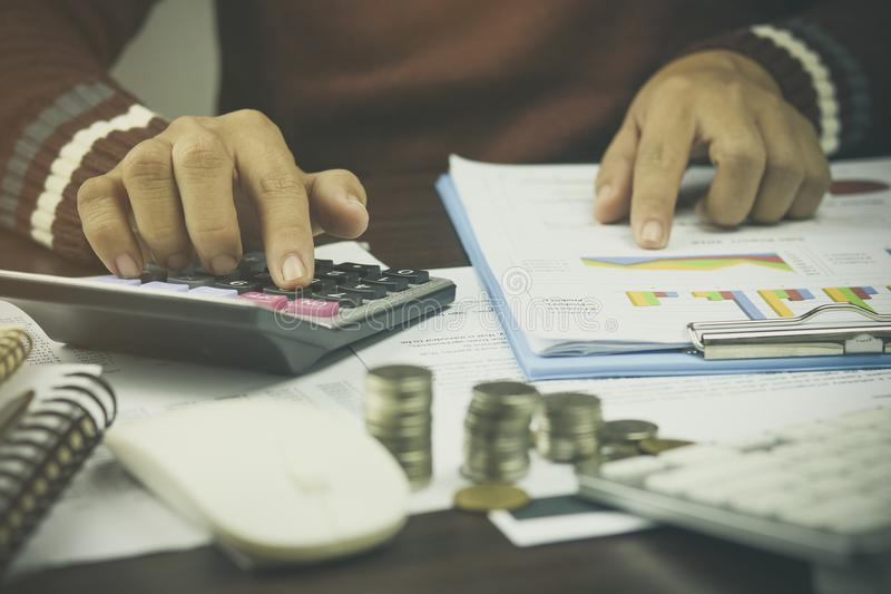 Ręka biznesmena writing, stosu menniczy pieniądze z obrachunkowej książki finanse i bankowość dla tła, pojęcie wewnątrz chodzi i obraz royalty free