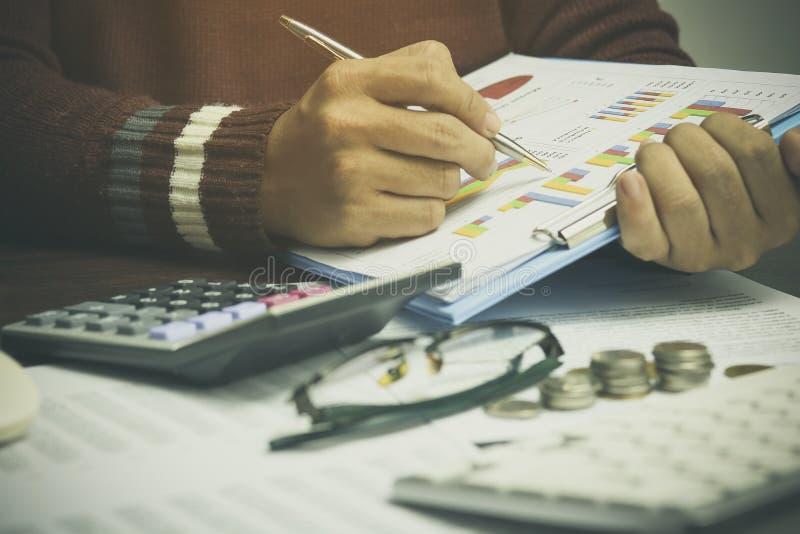 Ręka biznesmena writing, stosu menniczy pieniądze z obrachunkowej książki finanse i bankowość dla tła, pojęcie wewnątrz chodzi i zdjęcia royalty free