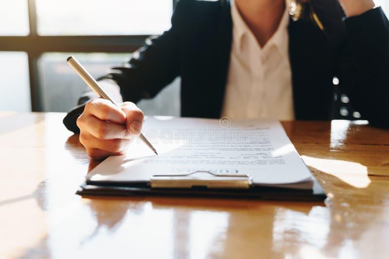 Ręka bizneswomanu obsiadanie przy stołem i pisać na biznesu kontrakcie w biurze obrazy royalty free