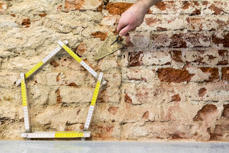 ręka buduje dom na ściana z cegieł tle fotografia royalty free