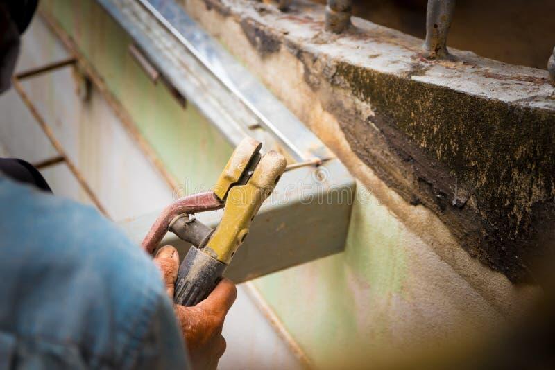 Ręka chwyt starszy spawacz pracuje stalowego spawu naprawę na dachowej wysokości Wybrana ostrość z płytką głębią pole obraz stock