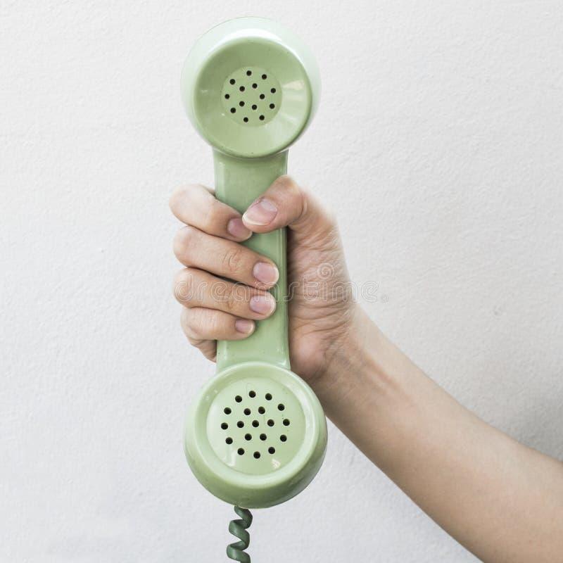 Ręka chwyta rocznika telefonu zielony kolor obraz stock