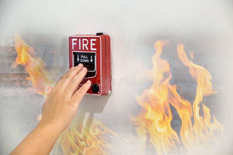 Ręka ciągnie pożarniczego alarma zmianę na białej ścianie jako tło dla przeciwawaryjnej skrzynki przy nowym fabrycznym budynkiem  obrazy royalty free