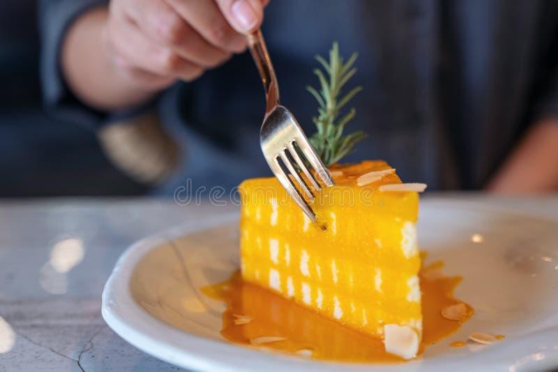 Ręka ciie kawałek pomarańcze tort jeść z rozwidleniem w kawiarni zdjęcia royalty free