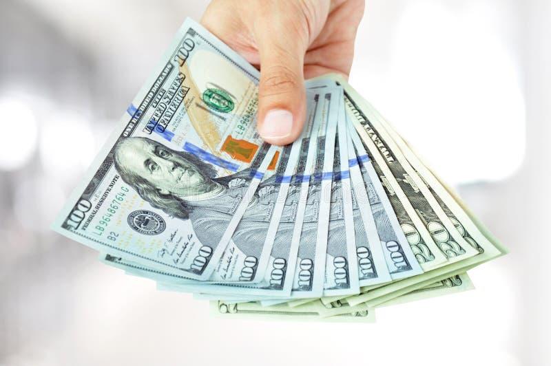 Ręka daje pieniądze - dolarów amerykańskich rachunki (USD) obrazy stock