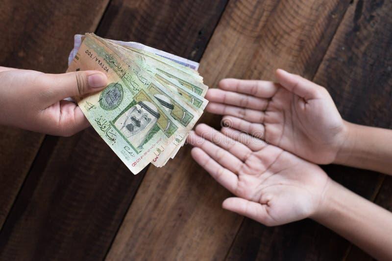 Ręka daje Saudyjskim Riyal banknotom obraz royalty free