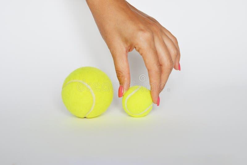 Ręka debiutant atleta wybiera małą tenisową piłkę na białym tle obrazy stock