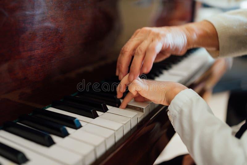 Ręka doświadczony pianista pomaga młodych uczni zdjęcia royalty free